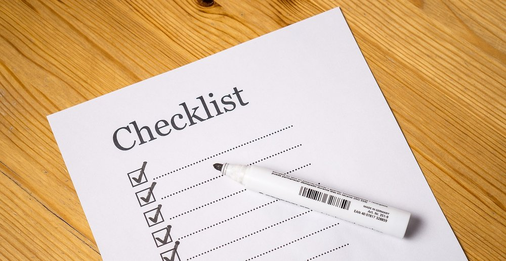 """paper headed """"Checklist"""" with pen and tick marks"""