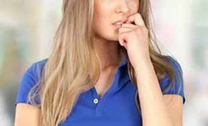 worried woman in blue blouse biting her nails
