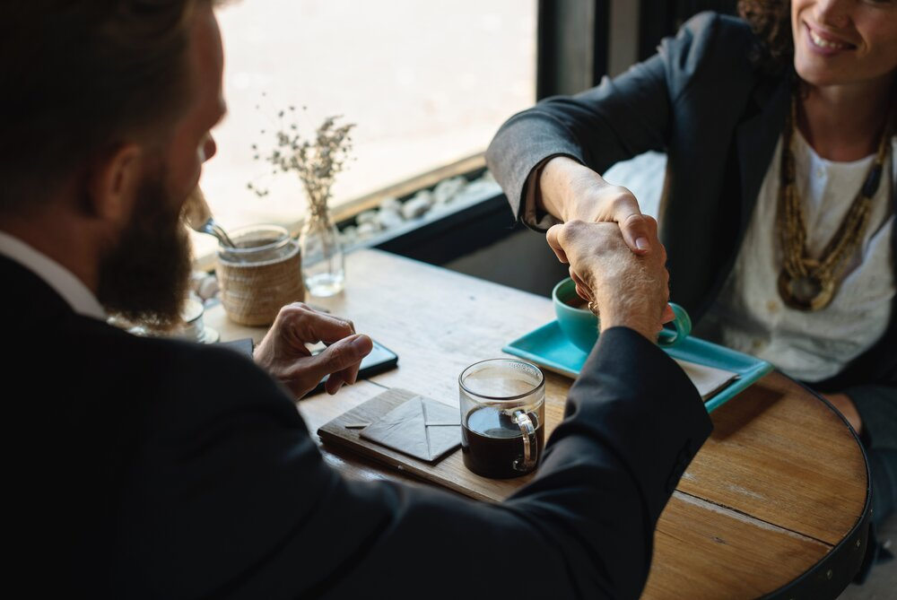 two business people shaking hands across a cafe table