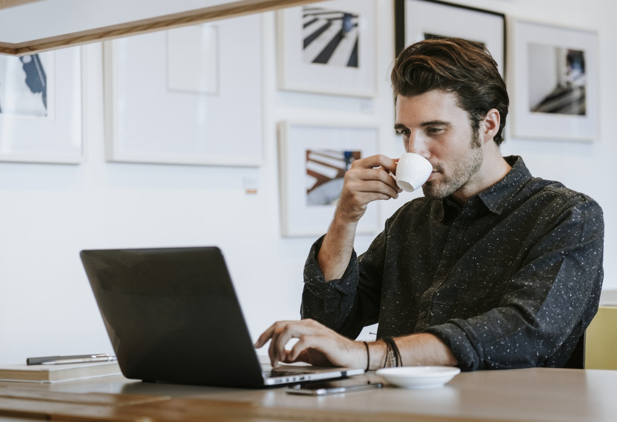 man at laptop sipping coffee
