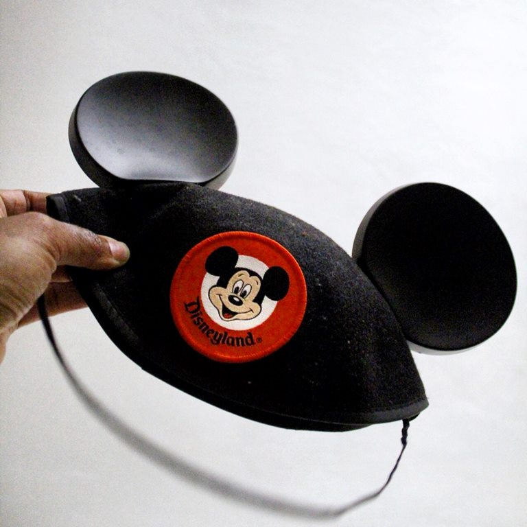 hand holding a Mickey Mouse hat with a Mickey Mouse badge on the front