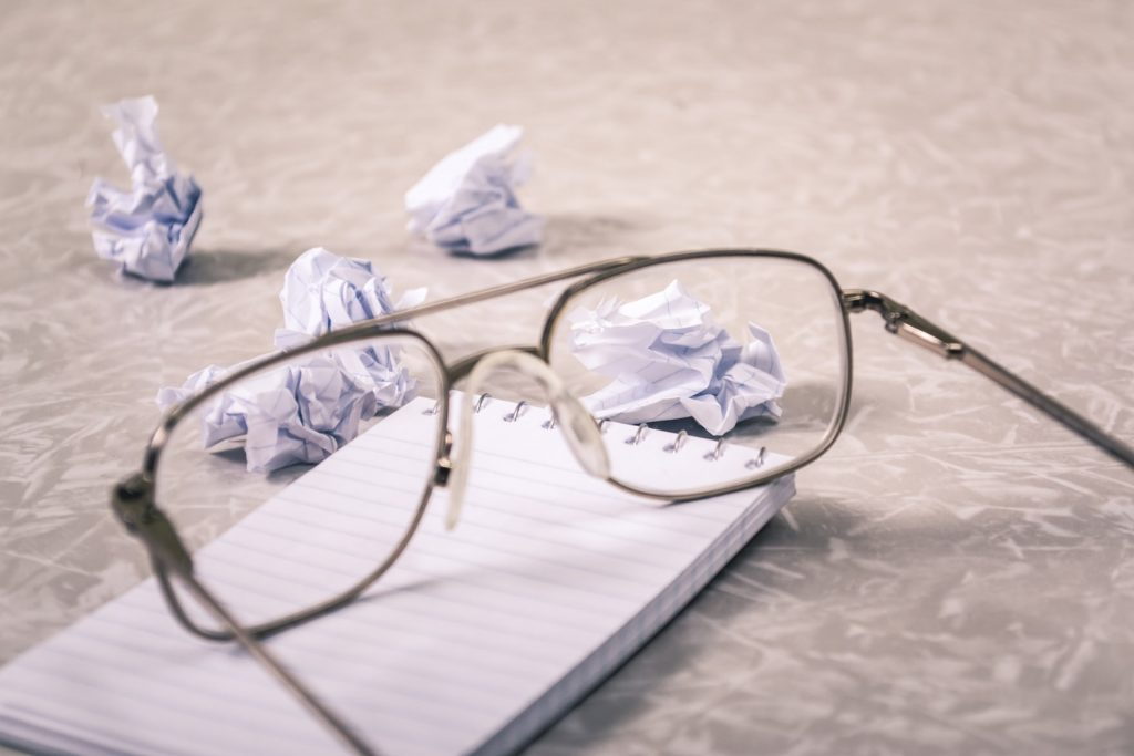 reading glasses resting on a blank notebook with screwed up paper