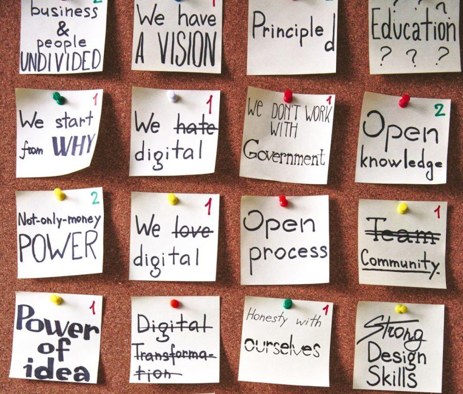 Pin board full of post it notes of business sayings