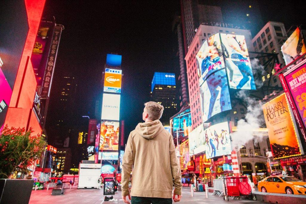 young man standing in Times Square looking at all the neon advertising