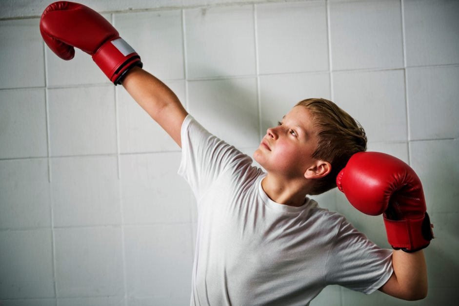 young boy wearing red boxing gloves striking a pose with fists in the air