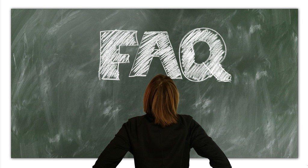 woman standing in front of blackboard with the letters FAQ written on it in chalk