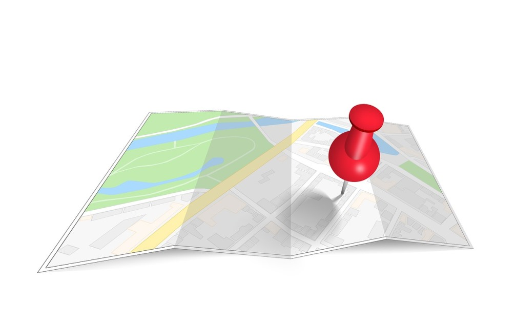a creased google map and a red mapping pin pinpointing a location on the map.
