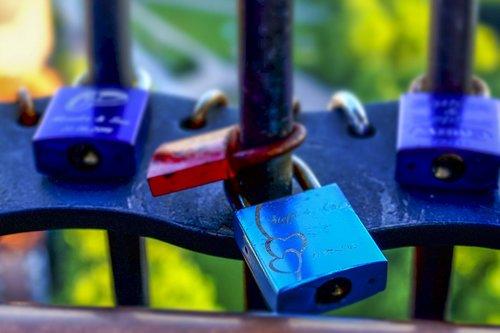close up of padlocks on a metal railing unlocking keywords