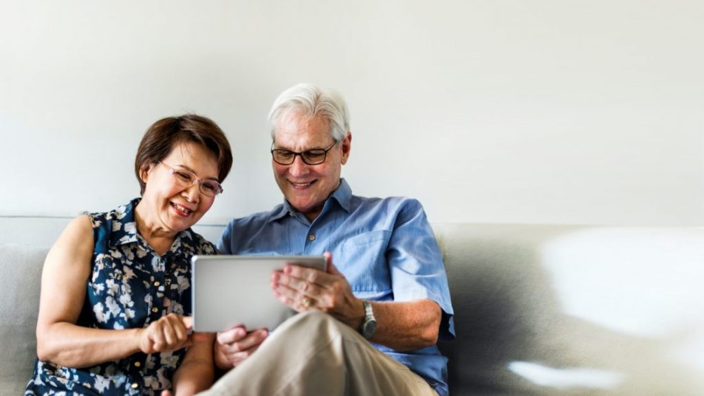 mature couple seated on sofa looking at accessible website on a tablet