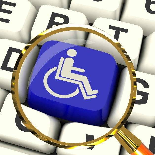 magnifying glass over a blue and white disabled logo on keyboard key