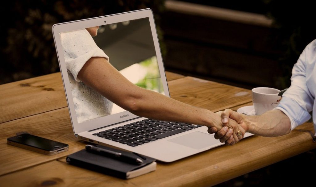 shaking hands through a PC screen